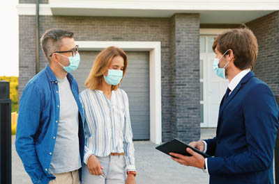 estate agent with man and woman outside of a house all wearing face masks